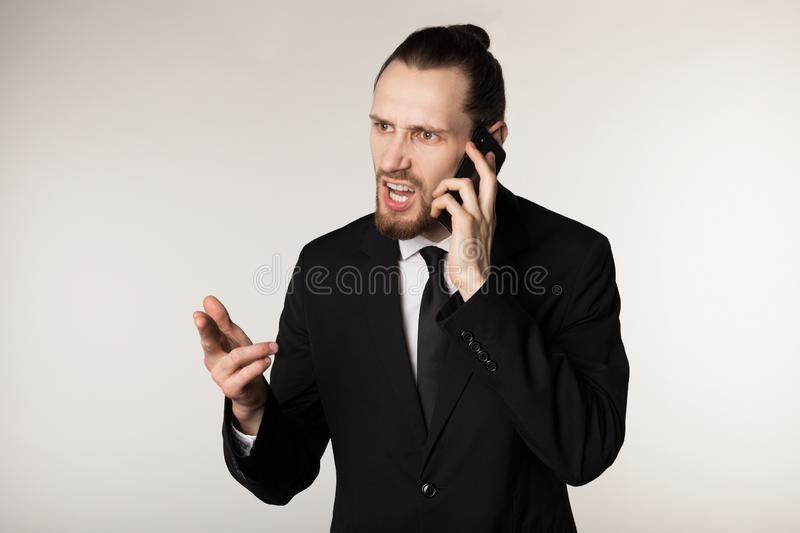 Waist up portrait of bearded young businessman in black suit that scolds his subordinate for not fulfiling the plan stock photos