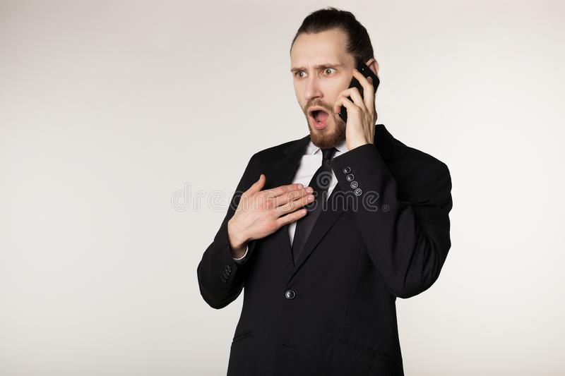 Waist up portrait of bearded young businessman in black suit surprised by the heard news from a business partner stock image