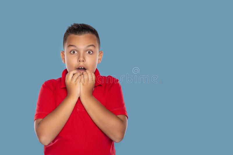 Waist up portrait of a boy with an expression on his face scared of something against on blue background with copy space in studio royalty free stock images