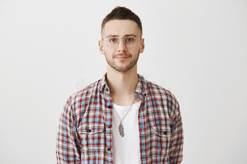 Waist-up portrait of calm and successful young businessman, wearing glasses and smiling at camera. Young entrepreneur royalty free stock images