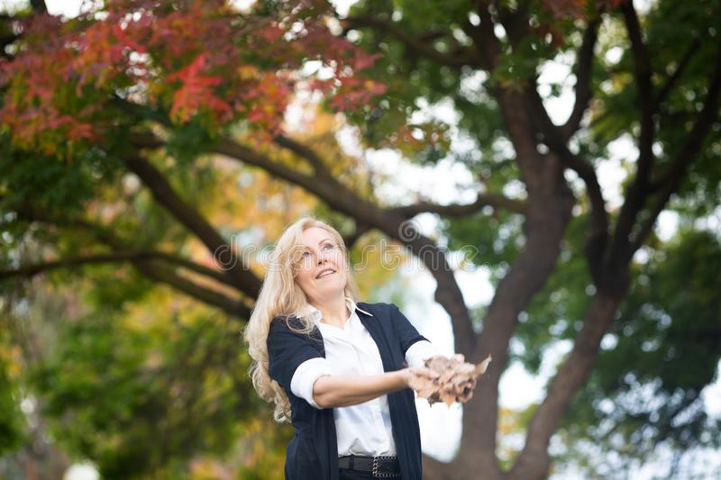 Waist up portrait of Caucasian blond woman throwing up in the air autumn yellow leaves, fall colors tree on background royalty free stock photography