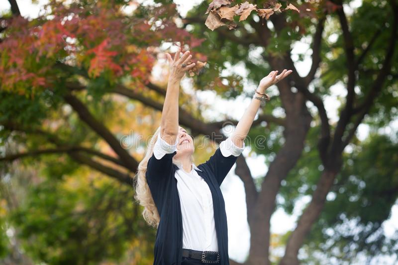 Waist up portrait of Caucasian blond woman throwing up in the air autumn yellow leaves, fall colors tree on background.  stock photos