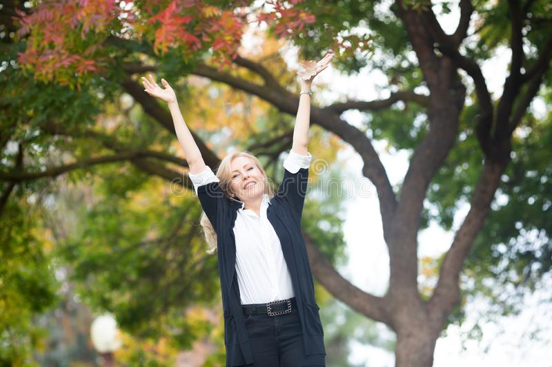 Waist up portrait of Caucasian blond woman throwing up in the air autumn yellow leaves, fall colors tree on background.  royalty free stock image