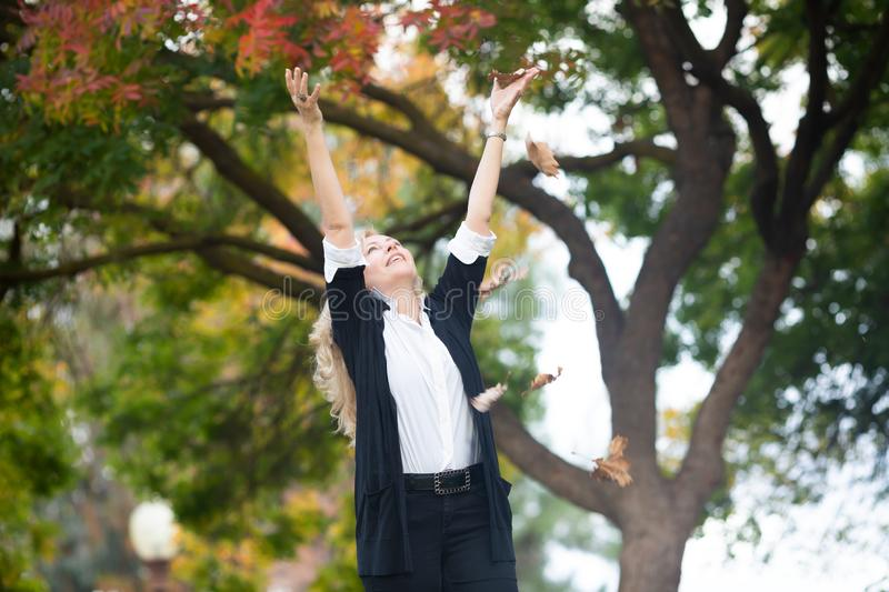 Waist up portrait of Caucasian blond woman throwing up in the air autumn yellow leaves, fall colors tree on background.  stock images