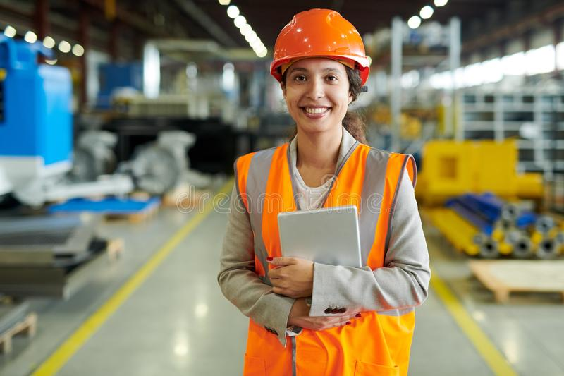 Cheerful Factory Worker Posing. Waist up portrait of cheerful young woman wearing hardhat smiling happily looking at camera while enjoying work in production royalty free stock images