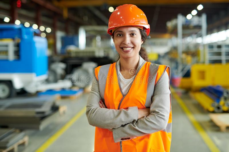 Confident Factory Worker Posing. Waist up portrait of cheerful young woman wearing hardhat smiling happily looking at camera while posing confidently in royalty free stock photo