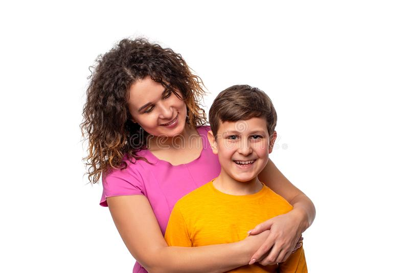 Shot of a cheriful young motherlovingly looking at her young son and huging him, isolated royalty free stock images