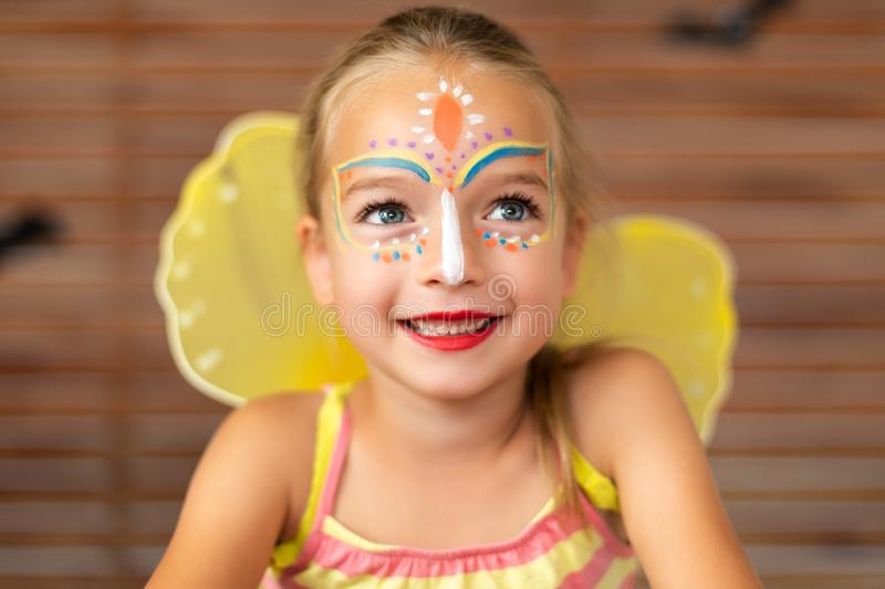 Waist up portrait of cute preschooler with DIY face paint wearing a butterfly halloween or carnival costume. Waist up portrait of cute preschooler with DIY face stock photography