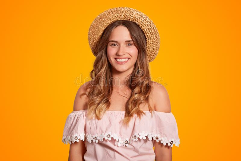 Waist up portrait of delighted beautiful young female traveller with broad smile, healthy pure skin, dressed in summer hat and blo stock photos