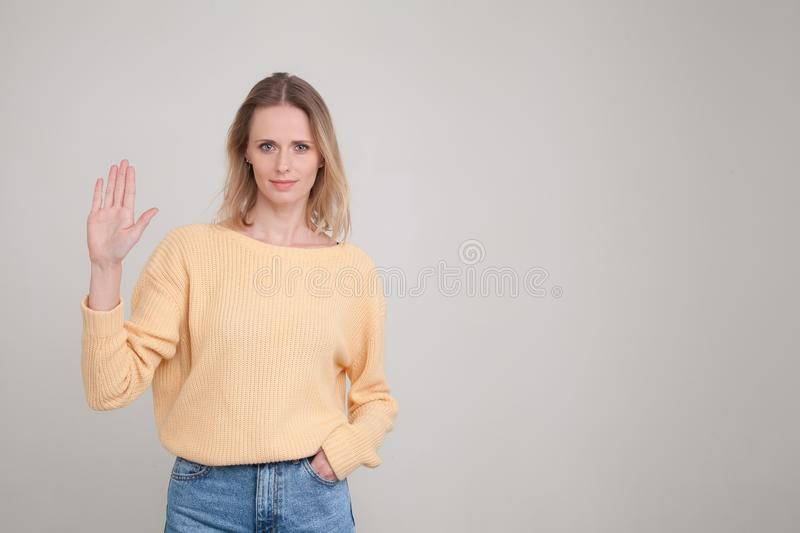 Waist up portrait go young blonde woman with calm emotion showing her hand palm to the camera, another hand is in the pocket. stock image
