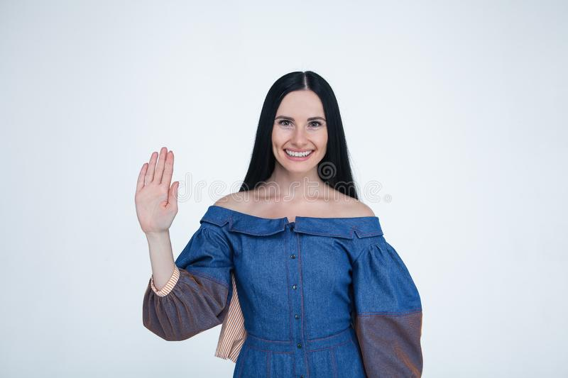 Waist up portrait go young brunette woman with smiling emotion showing her hand palm to the camera. dressed in jeans dress. poses royalty free stock photos
