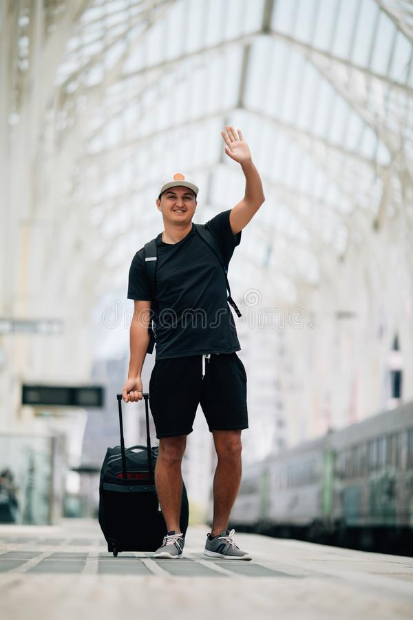 Portrait of handsome man raising hand waving looking away and smiling at train station stock photography