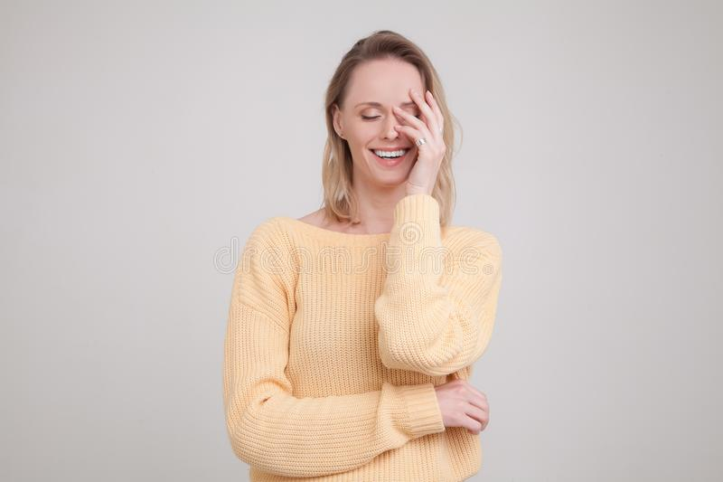 Waist-up portrait of happy blonde woman with pleased expression on her face, with eyes closed, keeping her hand on face. wearing stock photography