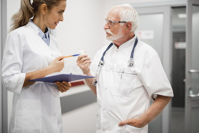 Doctor talking with nurse while holding pharmacy bottle with pills royalty free stock image