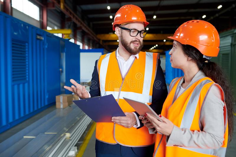 Inspector Talking to Woman at Factory. Waist up portrait of modern bearded businessman wearing hardhat talking to female factory worker while discussing royalty free stock images