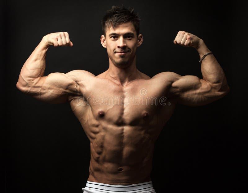 Waist-up portrait of muscular man flexing his biceps stock photos