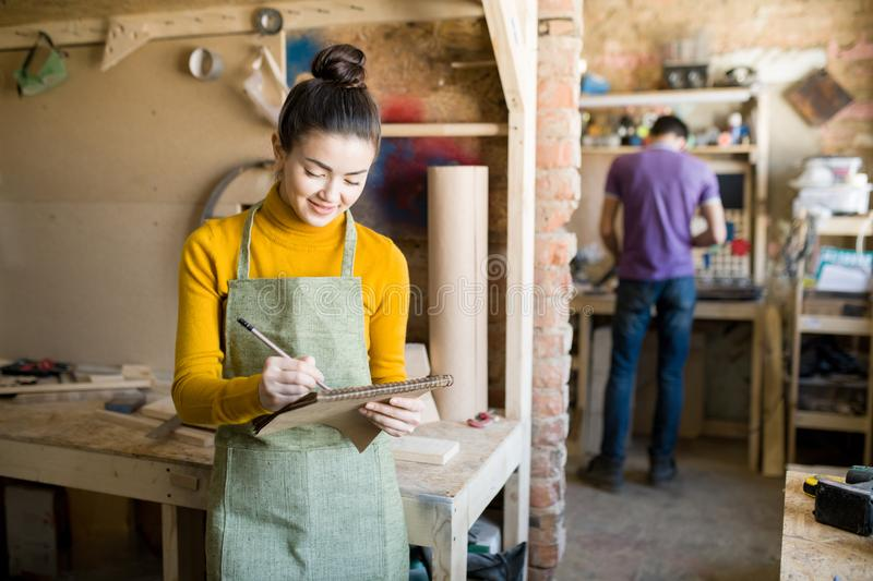 Cheerful Female Artisan in Workshop stock photos
