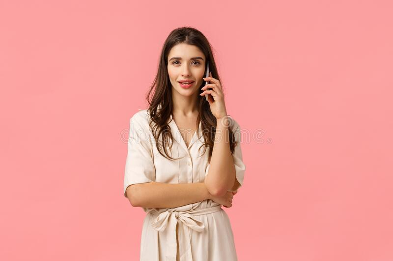 Waist-up portrait serious and gorgeous sassy young woman in dress, holding smartphone, talking on phone, calling friend stock images