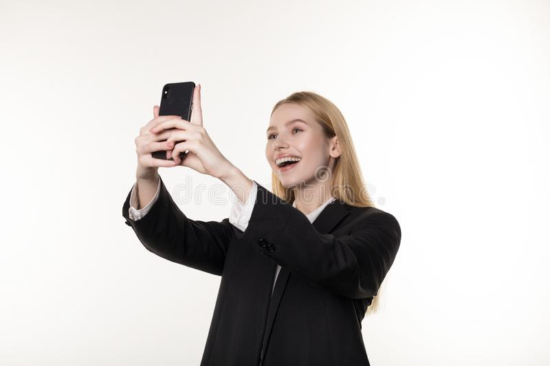 Waist up portrait of a smiling blonde businesswoman taking selfie with mobile phone stock image
