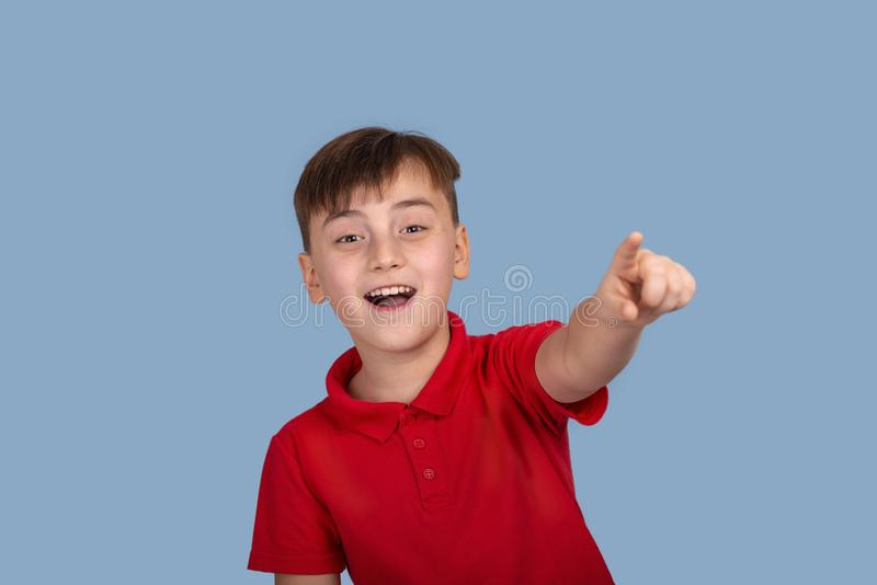 Studio shot of a smiling boy wearing a red shirt pulling a hand forward pointing to something on blue background in studio. Waist up portrait of a smiling boy stock image