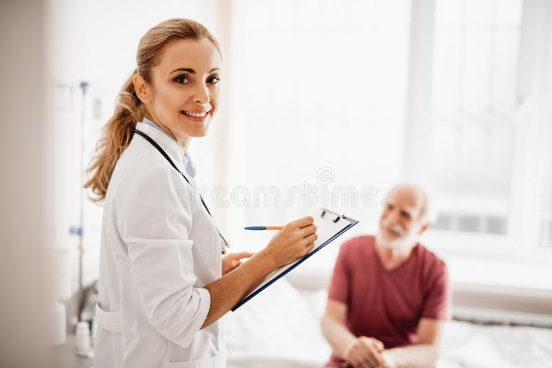 Beautiful female doctor with medical documents standing in hospital room royalty free stock photo