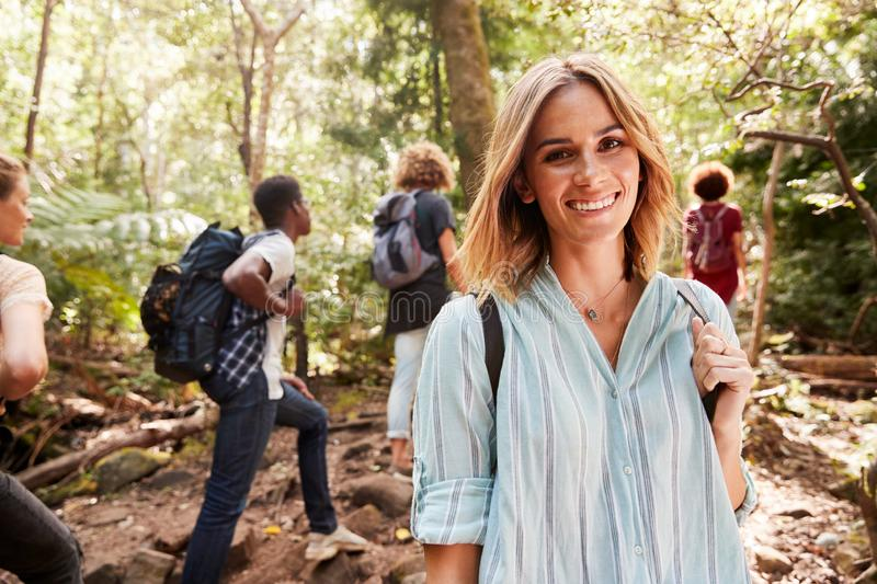Waist up portrait of smiling millennial white woman hiking in a forest with her friends, close up stock photos