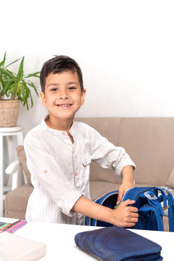 Waist up portrait of a smiling schoolboy. He collects a briefcase in school stock photography