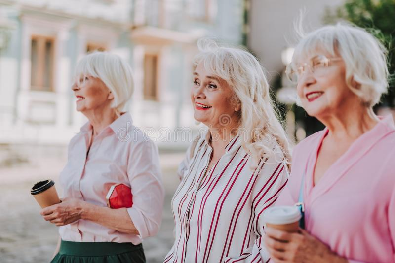 Smiling elderly women are drinking a coffee stock images