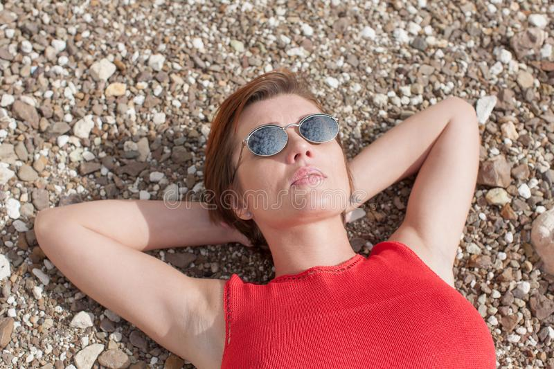 Waist-up portrait of woman lying on pebbles royalty free stock photos