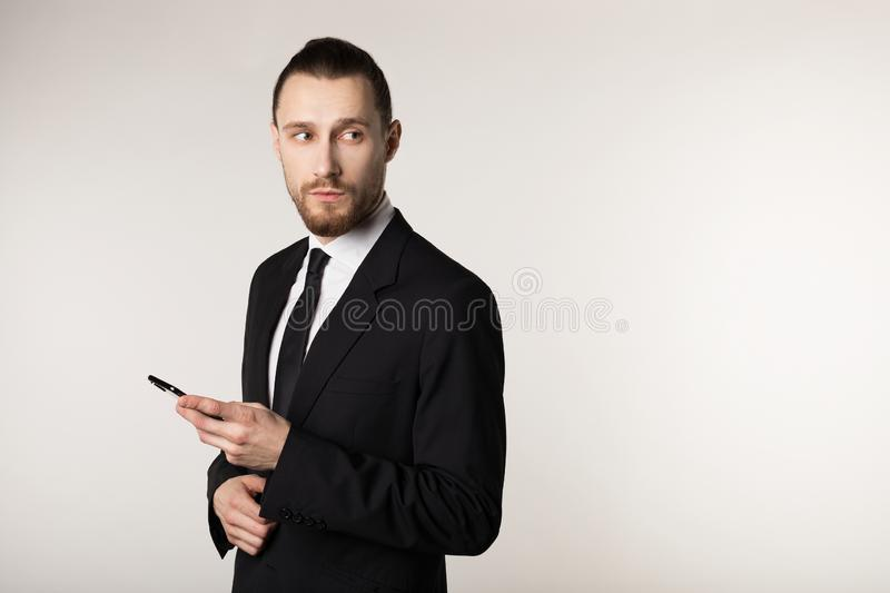 Waist up portrait of young bearded man in black suit standing with pen in hand, looking away stock photos