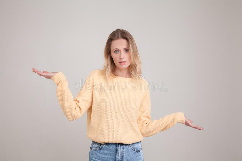 Waist-up portrait of young blonde woman with confused emotion, shrugs shoulders as she doesnt know the answer, being clueless and royalty free stock photography