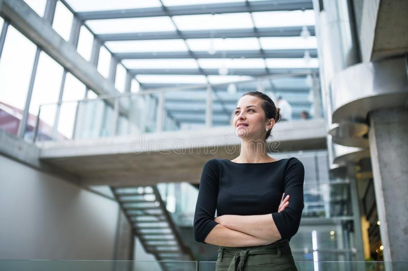 A portrait of young businesswoman standing in corridor outside office, arms crossed. royalty free stock photo