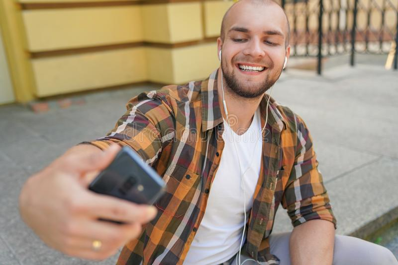 Waist up portrait of young good looking bold bearded guy is sitting outdoors on stairs in front of his house making selfie and stock images