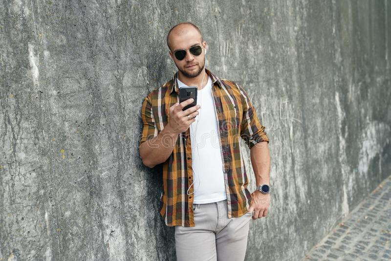 Waist up portrait of young good looking bold bearded guy standing outdoors against grey modern loft wall with call phone in his stock photos