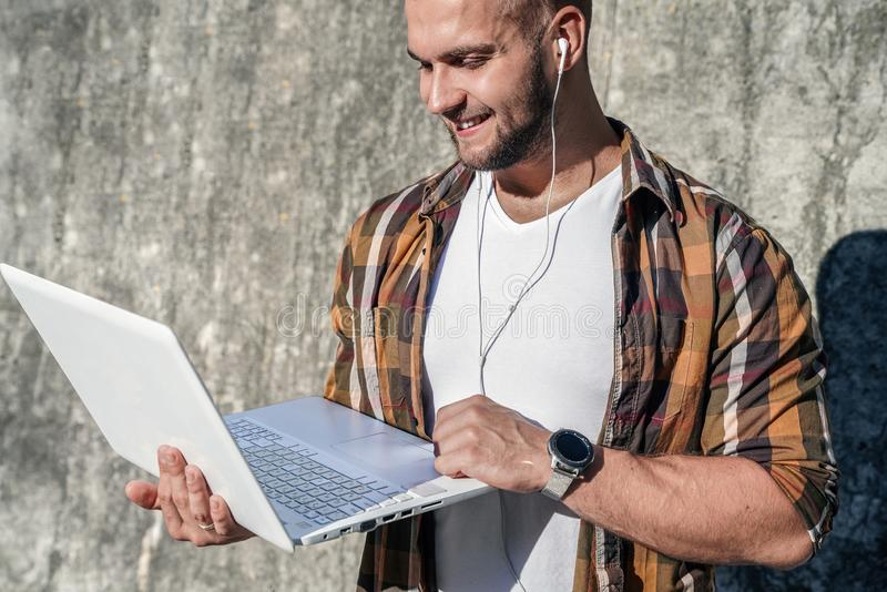 Waist up portrait of young good looking bold bearded hipster standing outdoors against grey modern loft wall with laptop and stock image
