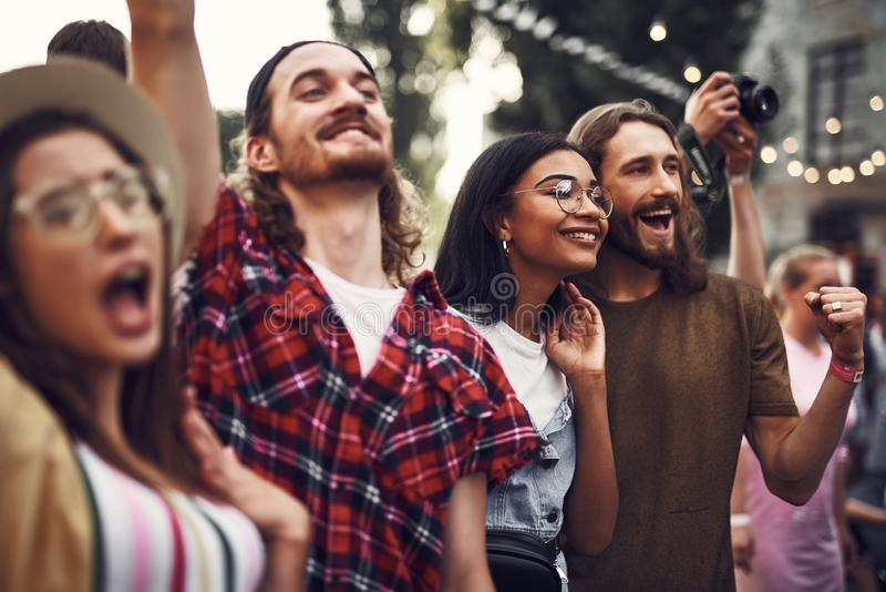 Group of cheerful hipsters spending time outdoors royalty free stock photography