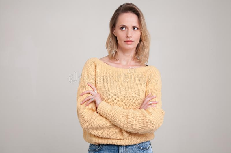 Waist-up portraite of blonde woman with puzzled face expression looks aside with her arms folded. wearing yellow sweater. poses royalty free stock photo