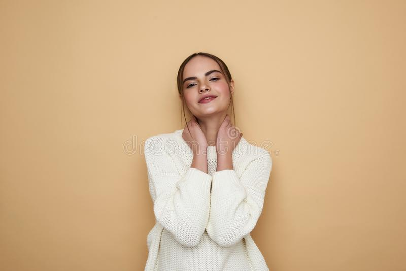 Waist up of relaxed young woman putting both hands on the neck royalty free stock image
