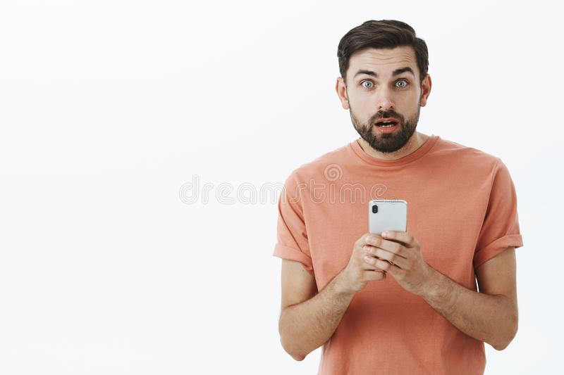 Waist-up shot of amazed and shocked stunned handsome caucasian guy with beard open mouth clueless holding smartphone royalty free stock image