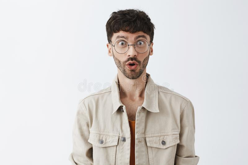 Waist-up shot of amazed and surprised emotive adult bearded guy in transparent glasses and beige jacket folding lips in royalty free stock photography