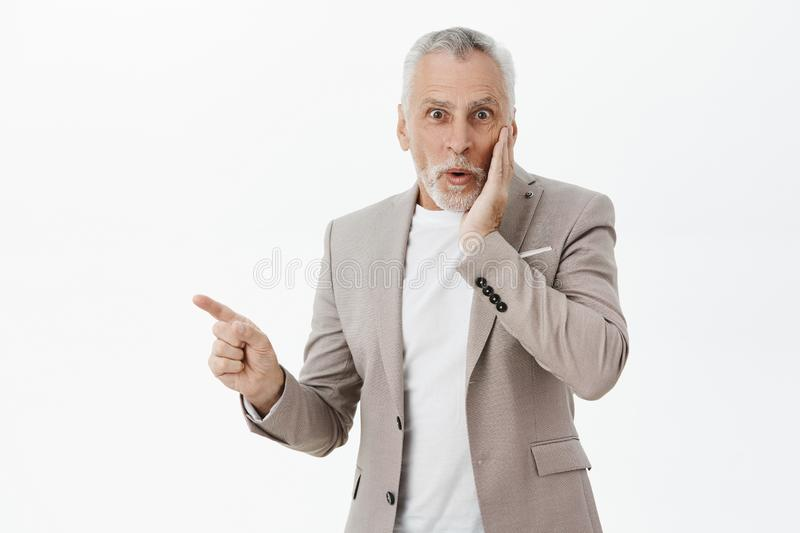 Waist-up shot of amused enthusiastic and happy good-looking fancy old man with beard and grey hair pressing hand to royalty free stock image