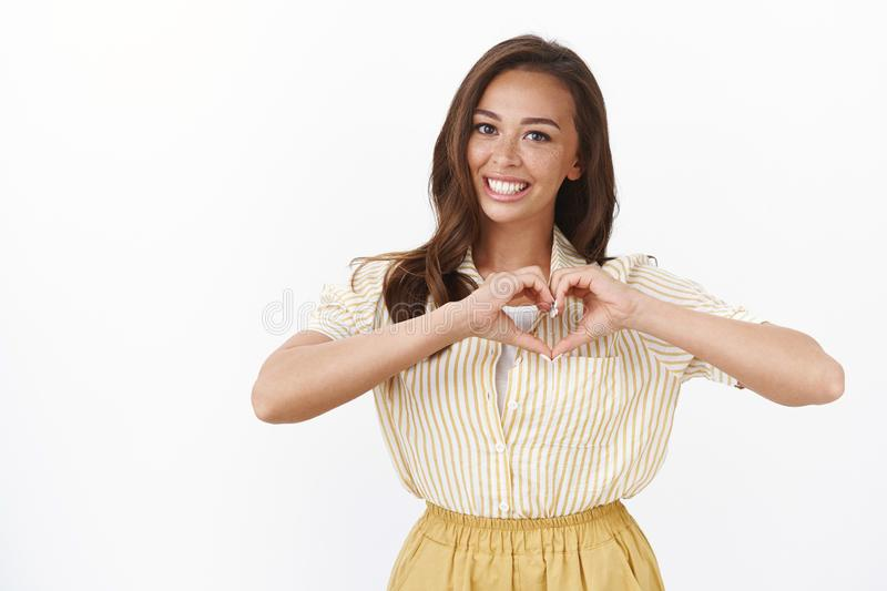 Waist-up shot attractive romantic young girlfriend confess in love, show heart sign and smiling toothy, adore partner. Making surprise, telling about feelings royalty free stock photos
