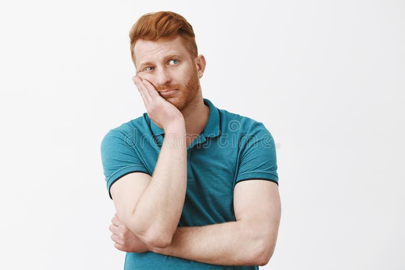 Waist-up shot of bored and tired gloomy redhead guy with bristle in green polo-shirt, leaning face on palm, staring stock photography
