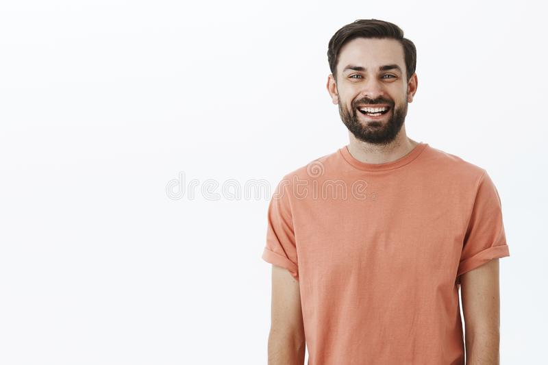Waist-up shot of bright and cheerful emotive friendly bearded 30s man with broad smile gazing satisfied and upbeat at stock photo