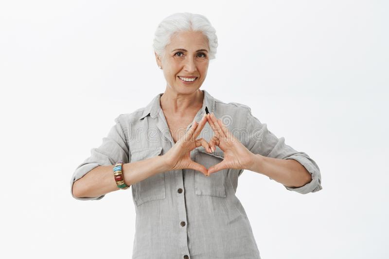 Waist-up shot of charming caring granny with grey hair in shirt showing heart sign over chest and smiling broadly loving stock image