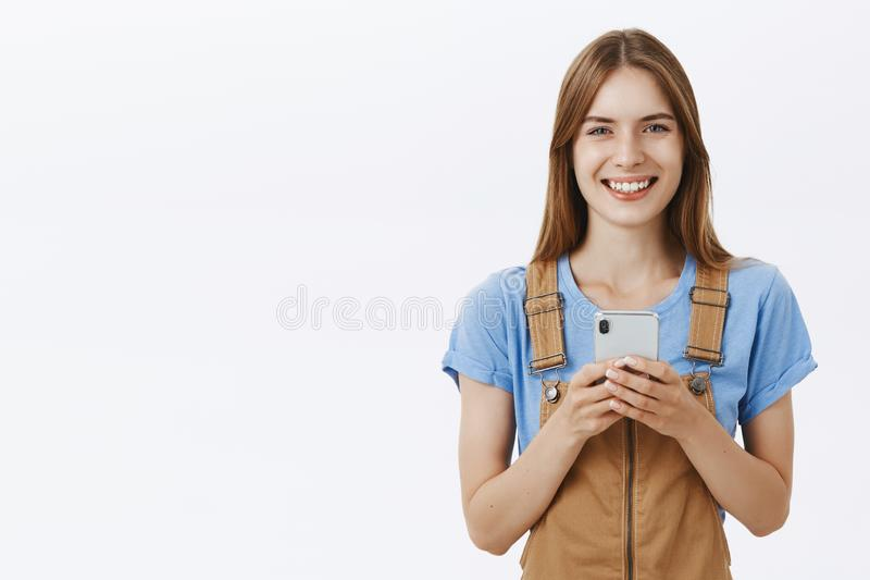 Waist-up shot of charming good-looking young female smartphone user in trendy overalls smiling joyfully with friendly. Expression holding cellphone edditing stock photos