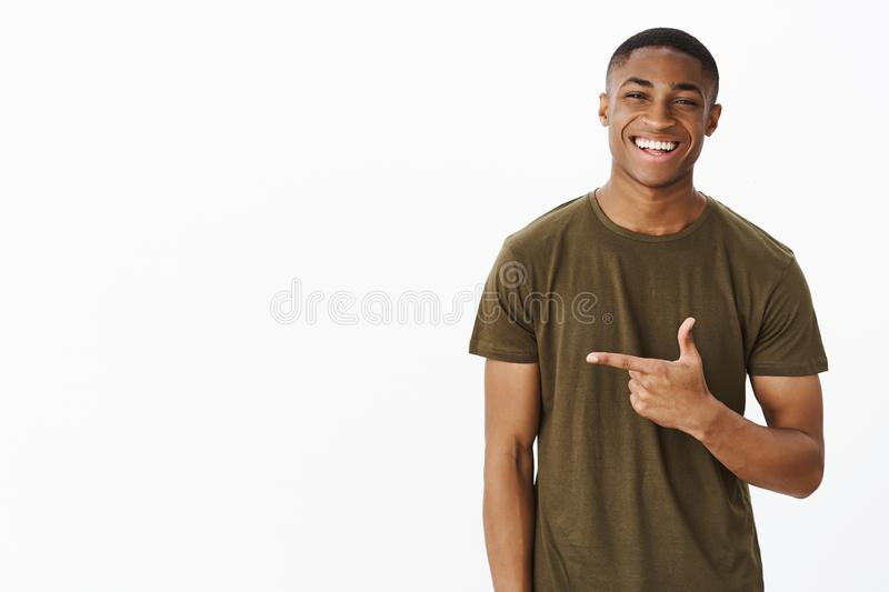 Waist-up shot of cheerful nice and handsome young african american man pointing left with index finger smiling and. Laughing joyfully, friendly chatting and stock image