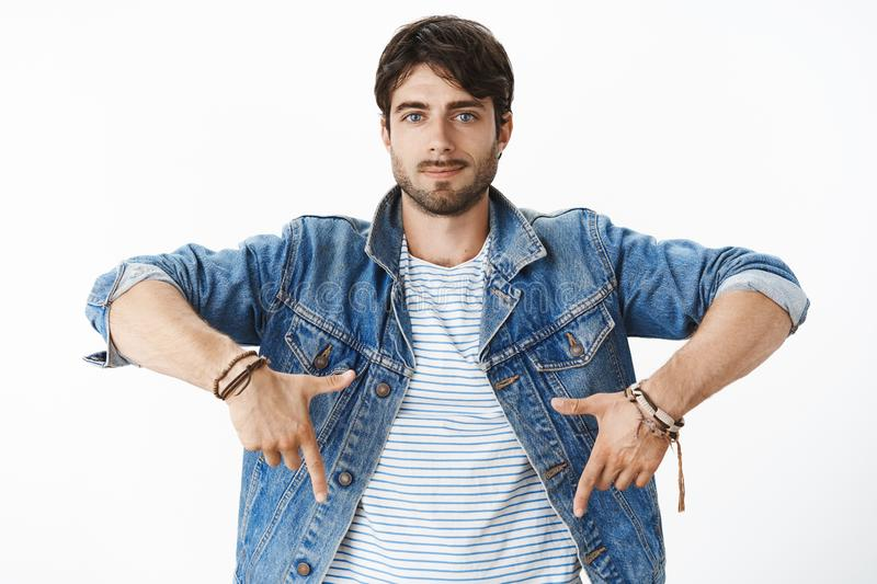 Waist-up shot of chill and joyful young handsome male entrepreneur in denim jacket with blue eyes and bristle smiling. Confident and assured pointing down stock photos