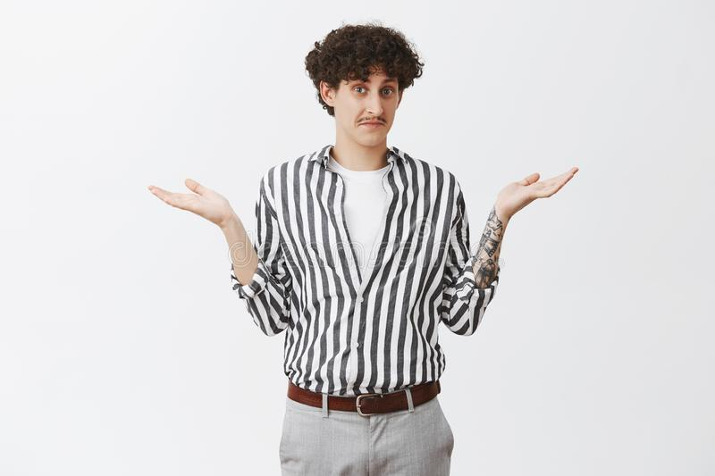 Waist-up shot of clueless good-looking and funny unaware guy with moustache and curly dark hair shrugging with spread. Palms having no idea feeling uncertain stock image