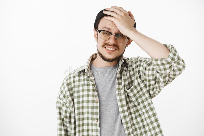 Waist-up shot of cocnerned and troubled upset guy with beard and moustache in black hipster beanie and glasses holding. Hand on head frimacing and frowning stock images